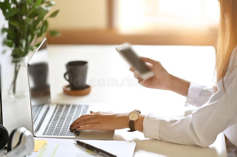 Frauen mit Laptop und Smartphone an der Schreibtisch stockfoto
