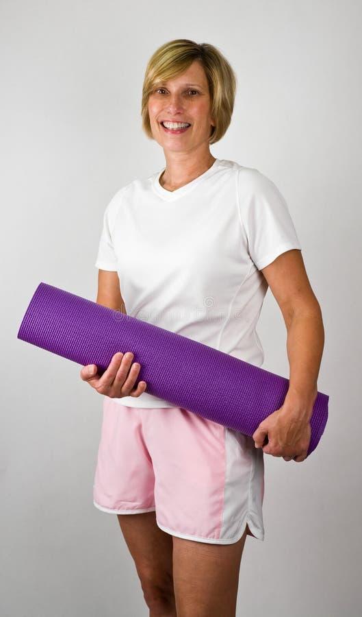 Frauen mit Yoga Polaties Matte stockfotos