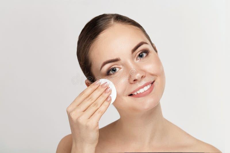 Frauen-Reinigungsgesicht mit weißer Auflage Schönes Mädchen, das Make-upweiße kosmetische Baumwollauflage entfernt lizenzfreies stockfoto