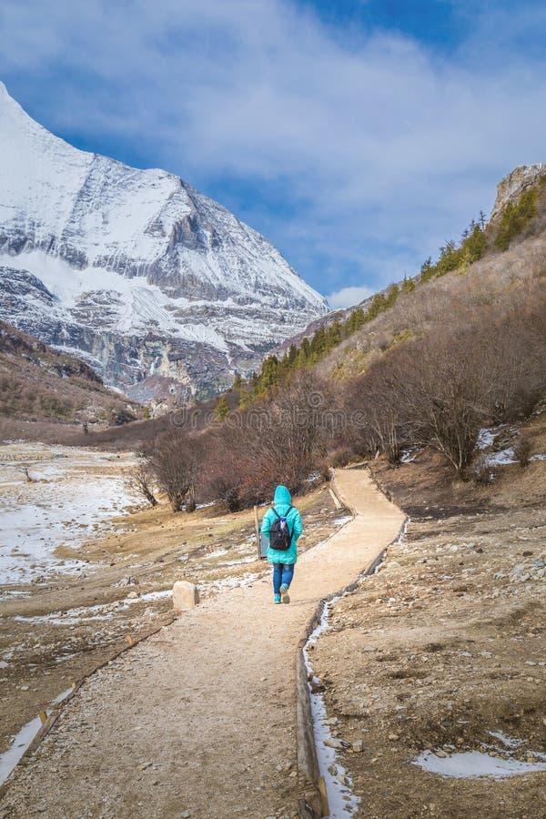 Frauen-Reisender mit dem Rucksack, der in den Bergen mit schönem wandert stockfotografie