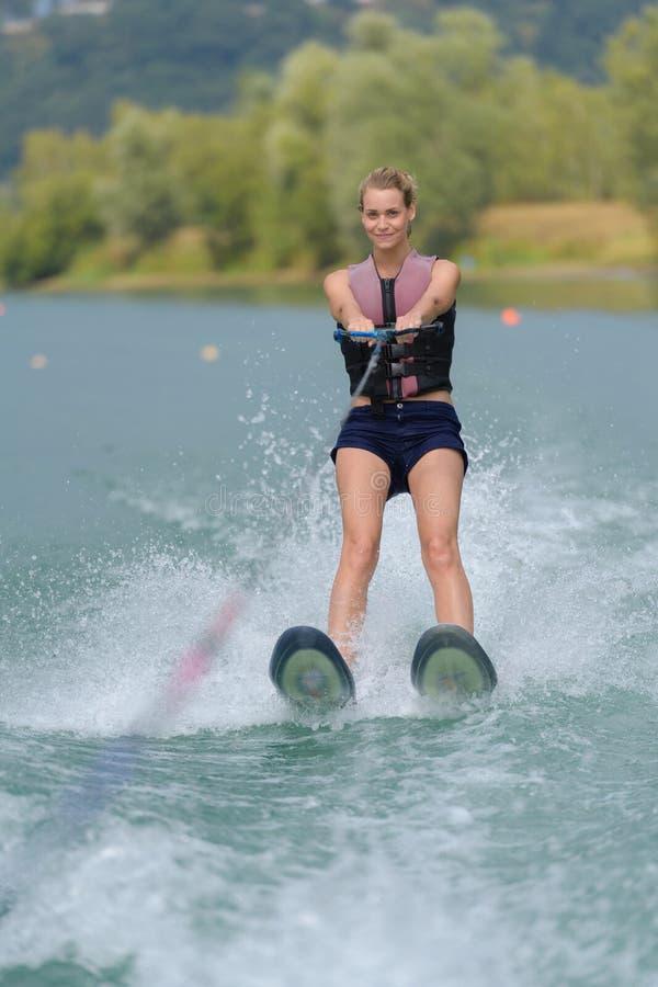 Frauen-Reiten-wakeboard der Junge recht dünnes im See stockbilder