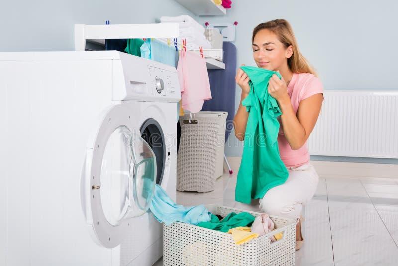 Frauen-riechende Kleidung nachdem dem Waschen lizenzfreie stockfotos