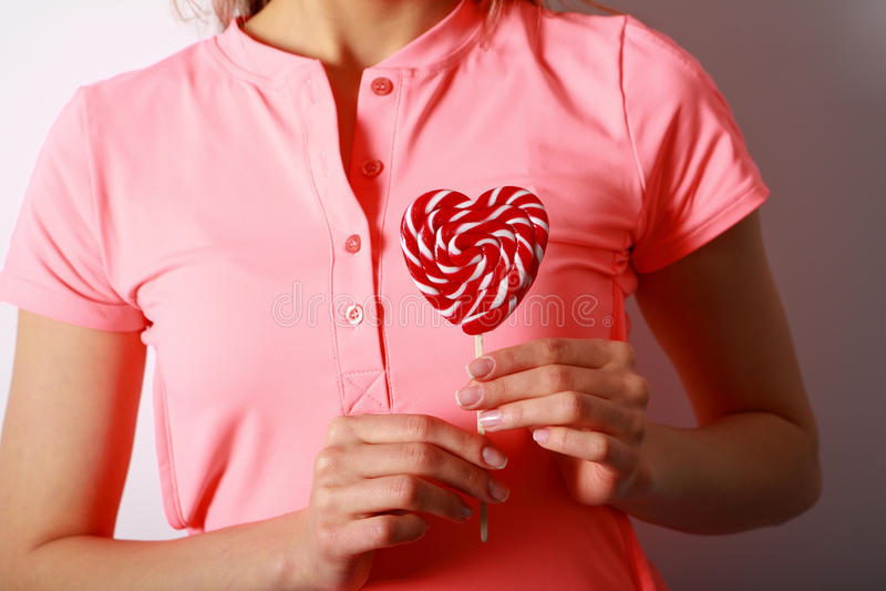 Frauen ` s übergibt das Halten eines Lutschers in Form des Herzens Geschenk für stockfotografie