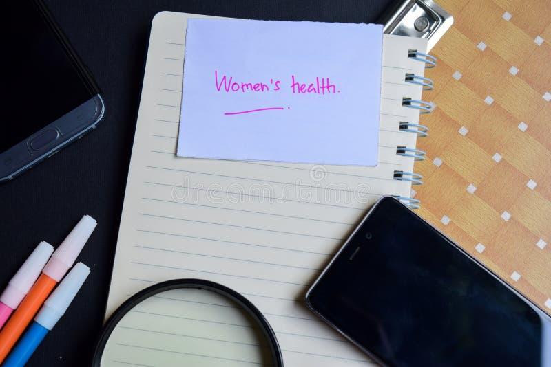 Frauen ` s Gesundheitswort geschrieben auf Papier Frauen ` s Gesundheitstext auf Arbeitsbuch, Technologiegeschäftskonzept lizenzfreies stockfoto