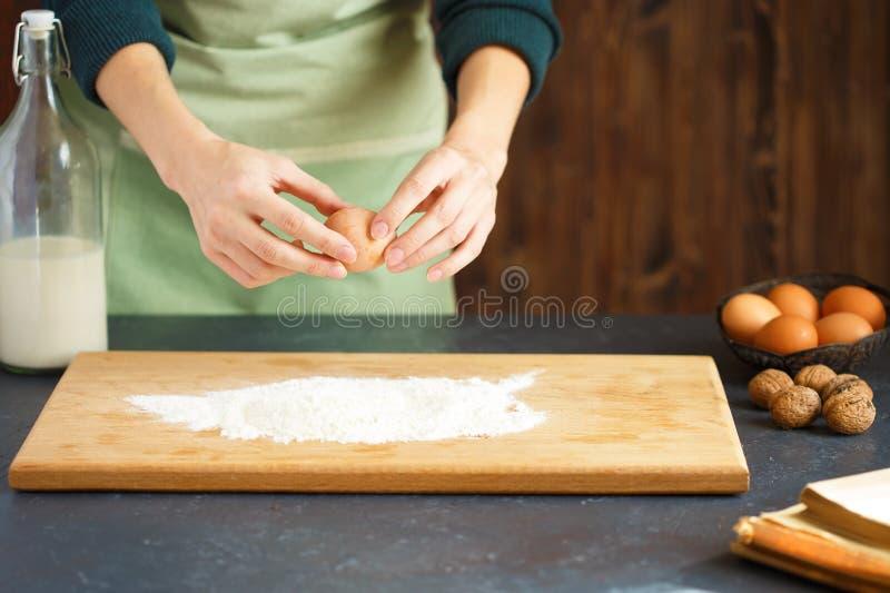 Frauen ` s Hände kneten den Teig Der Konditor fährt ein Ei in das Mehl Auf dem Holztisch backen stockbild