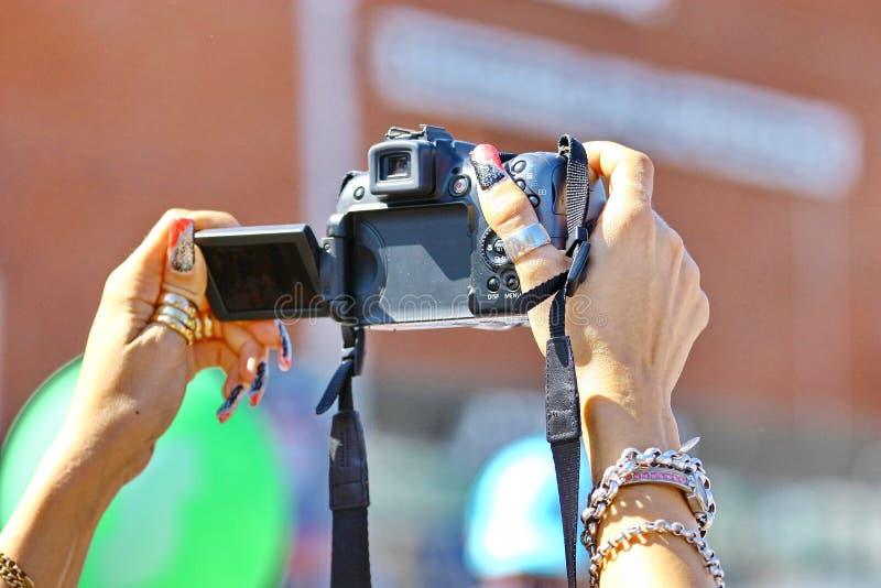 Frauen ` s Hände mit Armband und Maniküre halten Kamera stockbild