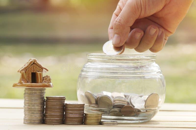 Frauen ` s Hand setzte Geldmünzen in Glasflasche für Abwehr- und Spendenkonzept für kaufendes Haus ein stockfotografie