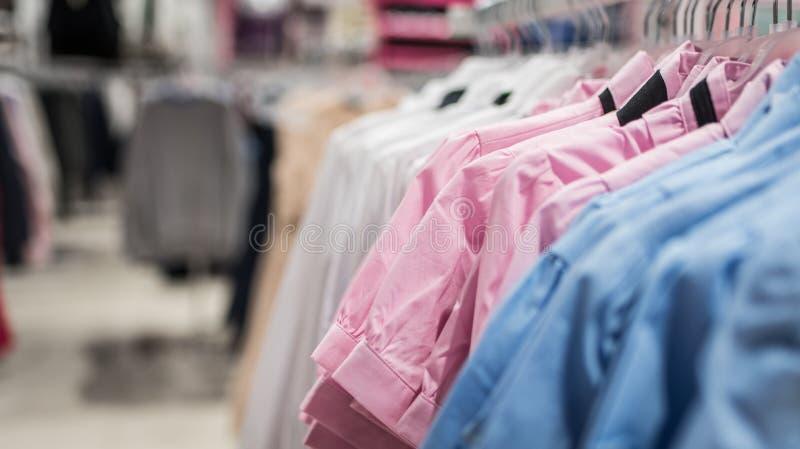 Frauen ` s Hemden und Blusen auf Aufhängern in einem Bekleidungsgeschäft lizenzfreie stockfotos
