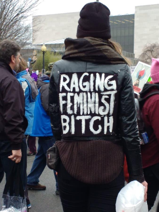 Frauen ` s März auf Washington DC, die Frau, die durch die Menge trägt eine Jacke geht, beschriftete ` rasendes feministisches ` lizenzfreie stockfotos