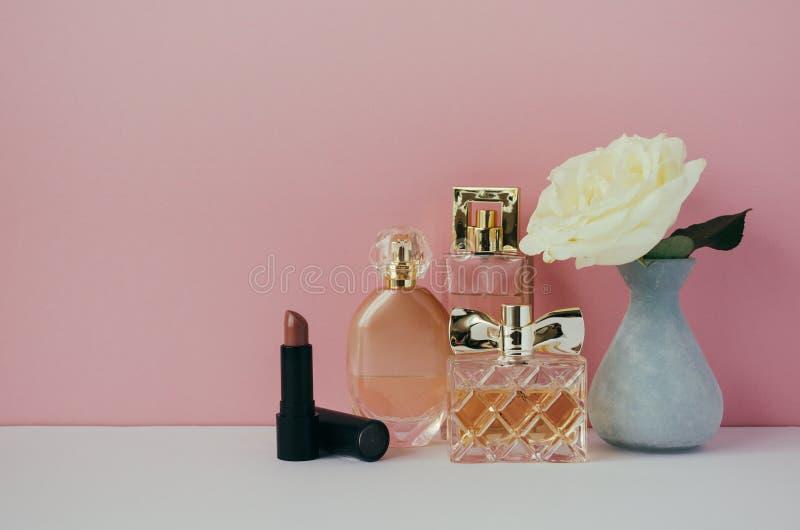Frauen ` s Parfüm, Lippenstift, Weißrose in einem Vase im Regal Unbedeutender Innenraum stockbilder