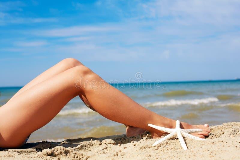 Frauen ` s schöne Sonnenbräunebeine auf dem Strand lizenzfreies stockfoto