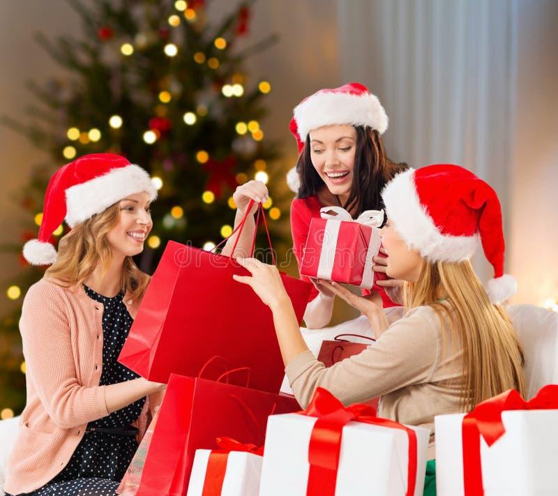 Frauen in Sankt-Hüten mit Geschenken auf Weihnachten stockfotografie