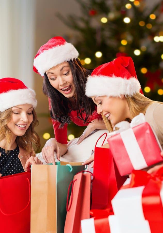 Frauen in Sankt-Hüten mit Geschenken auf Weihnachten lizenzfreies stockbild