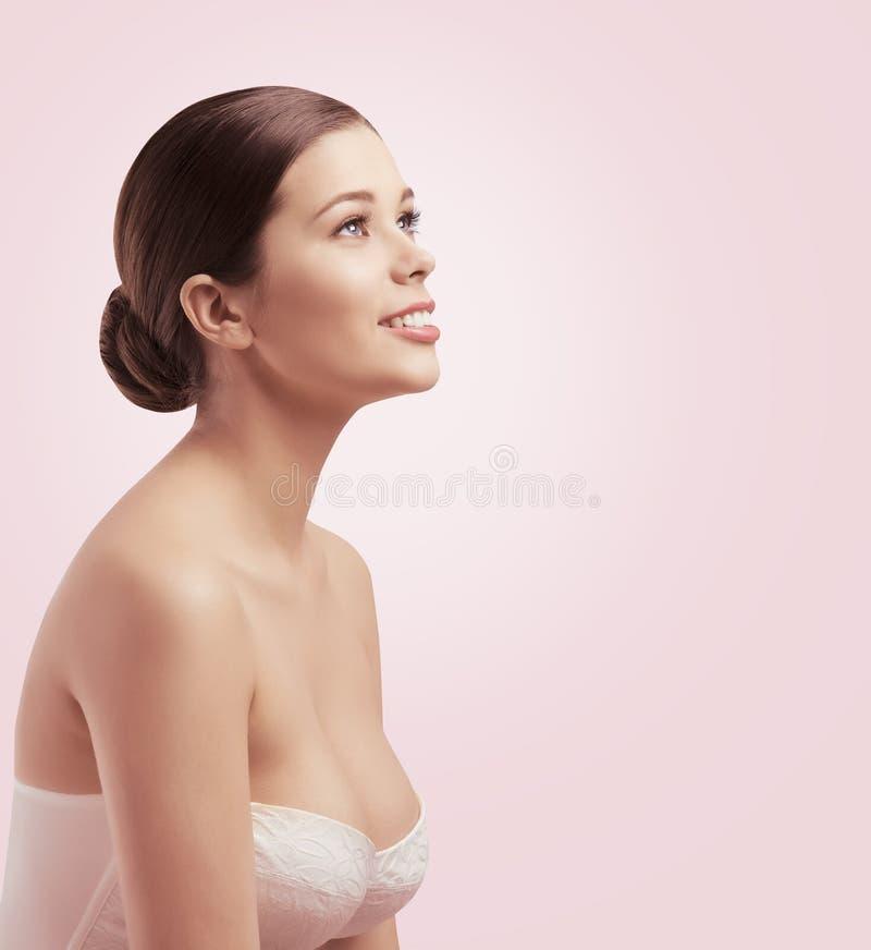 Frauen-Schönheits-Gesicht, Mädchen-Brust-Hautpflege, Brötchen-Haar lizenzfreie stockbilder