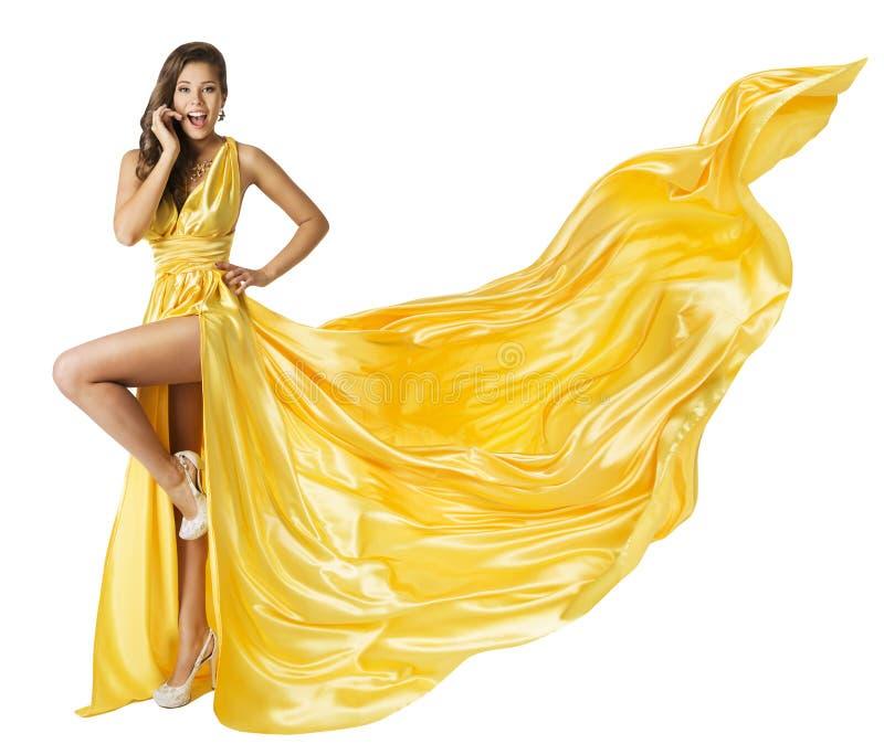 Frauen-Schönheits-Mode-Kleid, schönes Mädchen, wenn das gelbe flatternde Kleid geflogen wird und auf den ein Bein-hohen Absätzen, lizenzfreies stockfoto