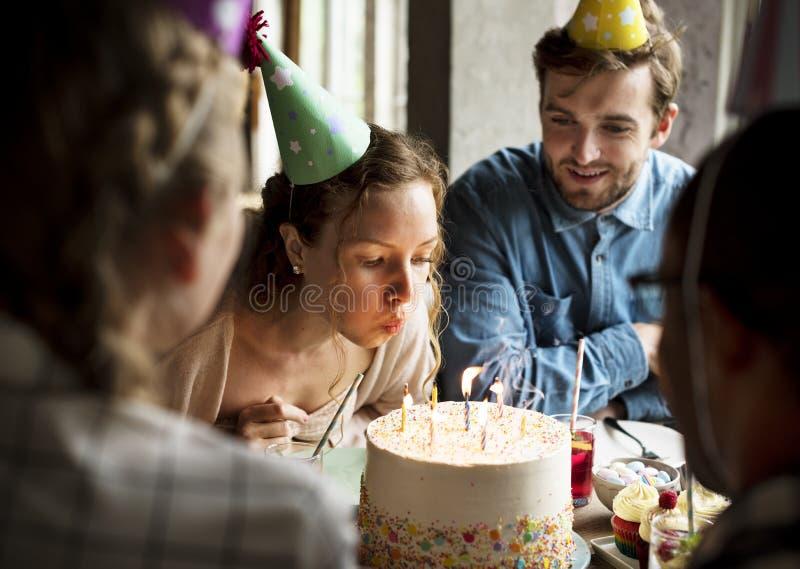 Frauen-Schlagkerzen auf Kuchen auf ihrer Geburtstagsfeier-Feier stockbild