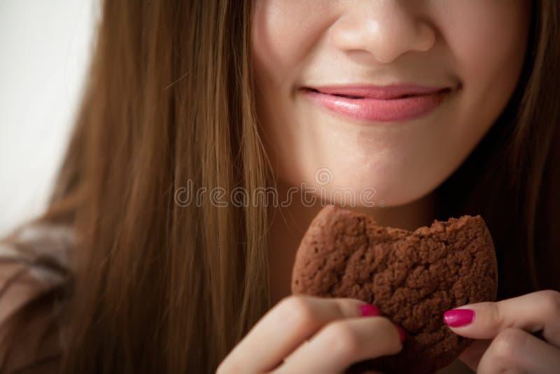 Frauen schmecken köstliche Plätzchen lizenzfreie stockbilder