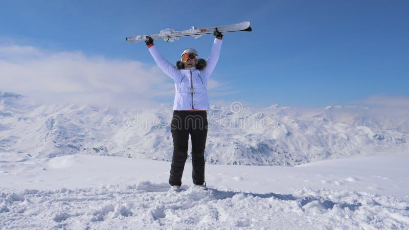Frauen-Skifahrer steht auf dem Steigungs-Berg, angehoben Ski And Waves Them lizenzfreie stockfotografie