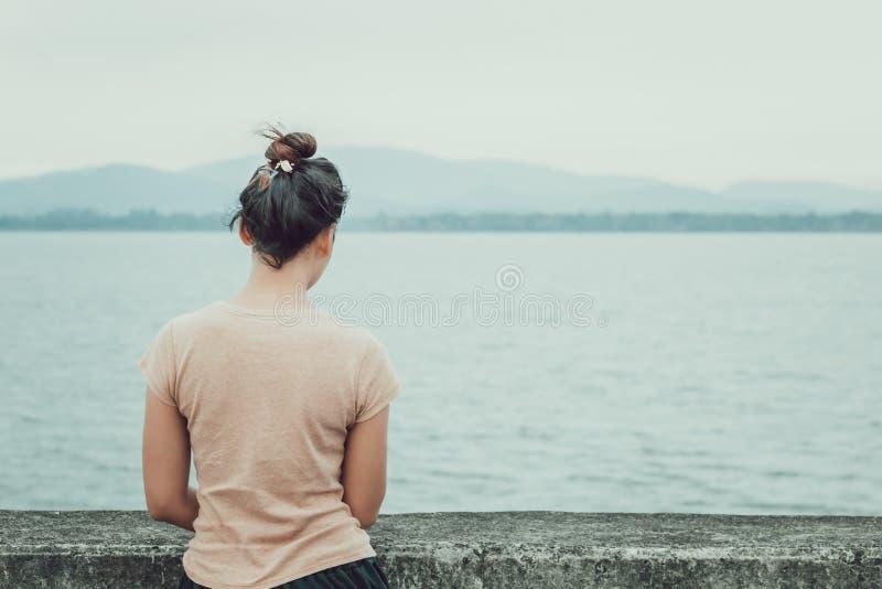 Frauen stehen nahe dem Wasser und dem Berg zurück allein stockfotos