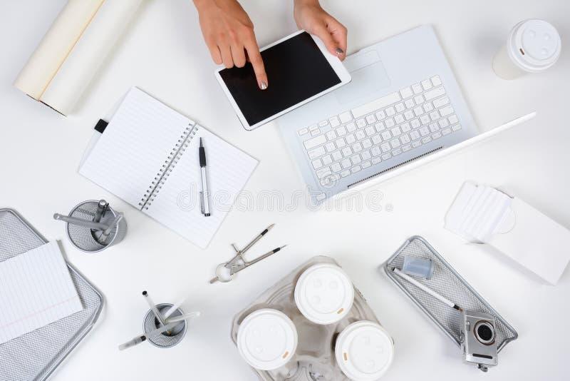Frauen-Tablet-Computer-Weiß-Schreibtisch lizenzfreie stockfotografie