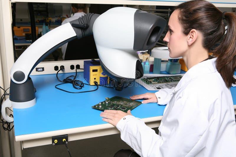 Frauen-Techniker mit Mikroskop lizenzfreie stockbilder