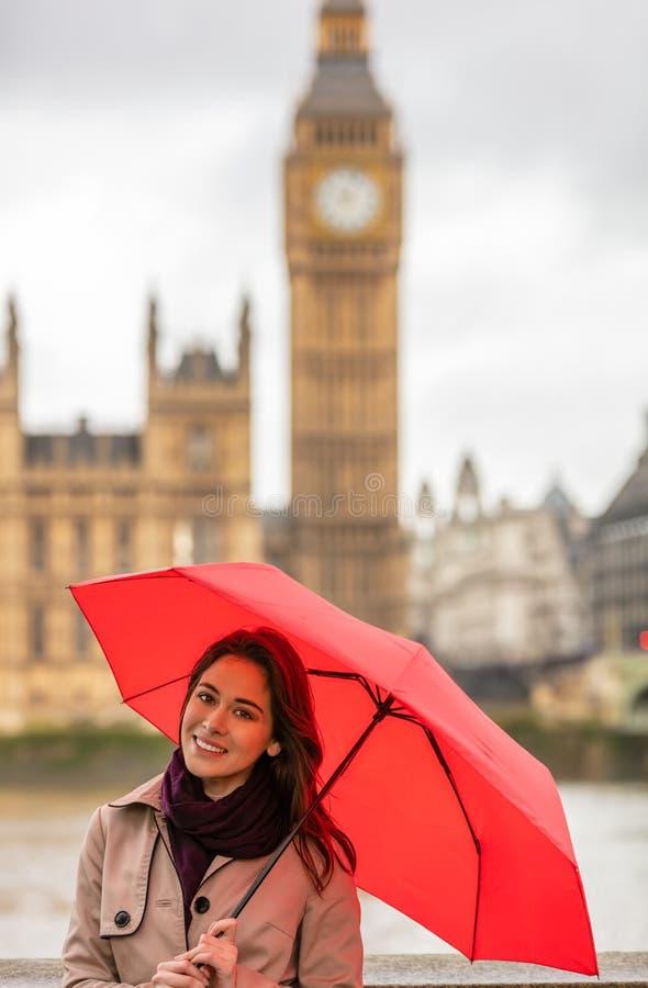 Frauen-Tourist mit Regenschirm durch Big Ben, London, England stockfotografie