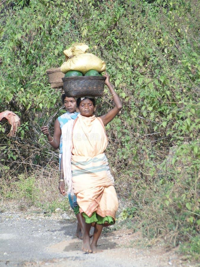 Frauen tragen Waren auf ihrem Kopf stockfotografie