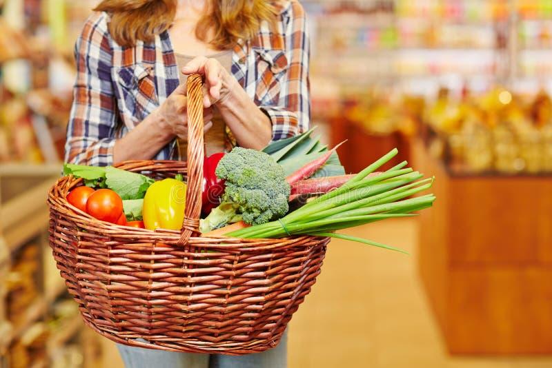 Frauen-tragender Einkaufskorb im Supermarkt stockbild