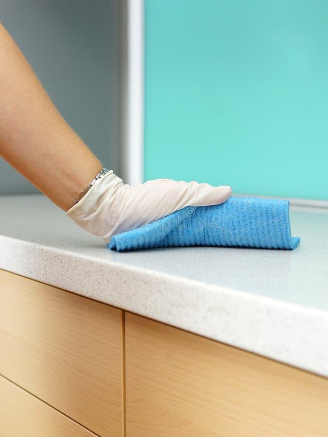 Frauen-tragendes Schutzblech-Reinigungs-Küche worktop stockfotografie