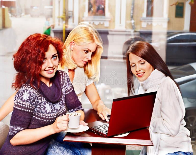 Frauen an trinkendem Kaffee des Laptops in einem Café. stockfotografie