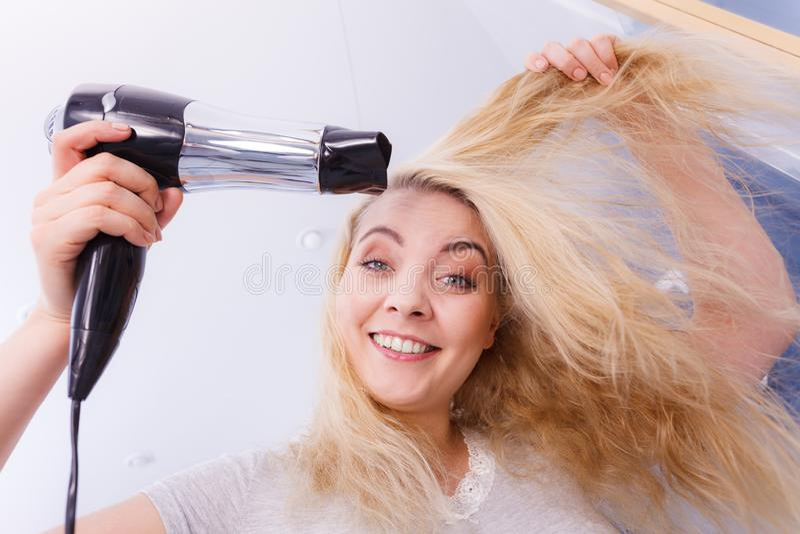Frauen-trocknendes Haar im Badezimmer stockfoto