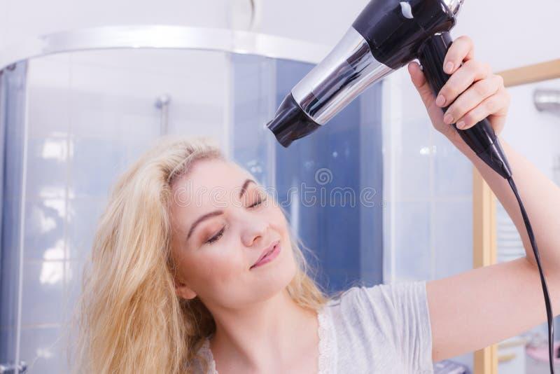 Frauen-trocknendes Haar im Badezimmer stockfotografie