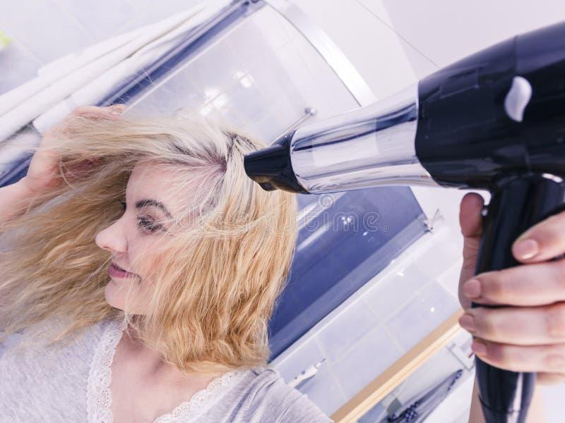 Frauen-trocknendes Haar im Badezimmer stockbild