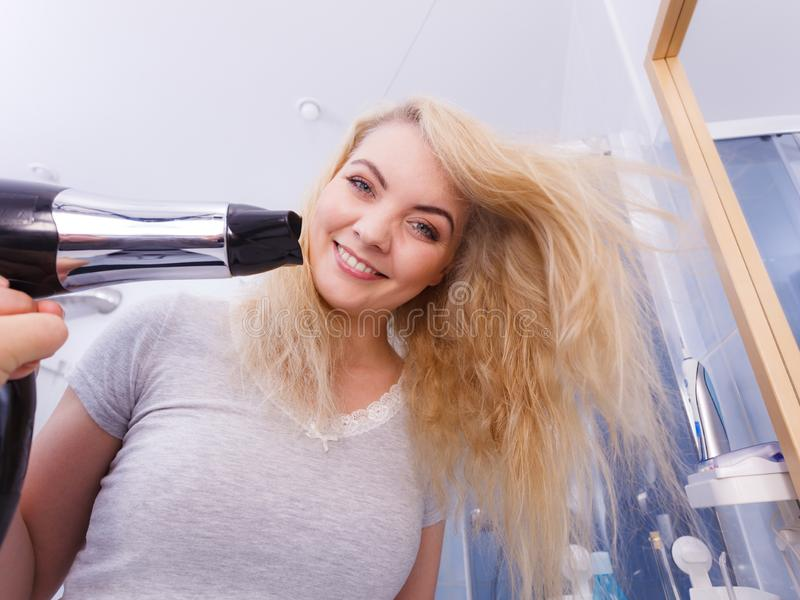 Frauen-trocknendes Haar im Badezimmer lizenzfreies stockbild