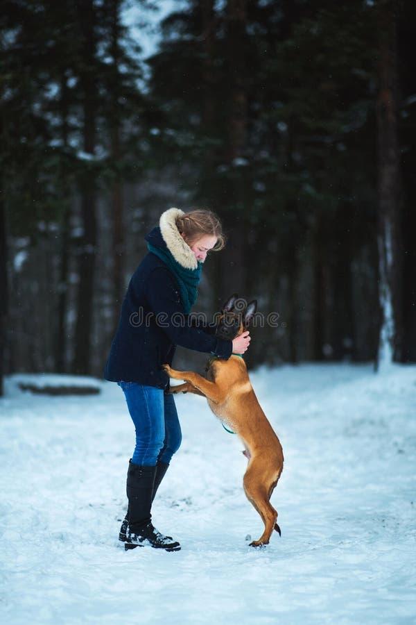 Frauen und belgischer Schäfer Dog im Winter Schneiender Hintergrund Gefrorener Wald lizenzfreie stockfotografie