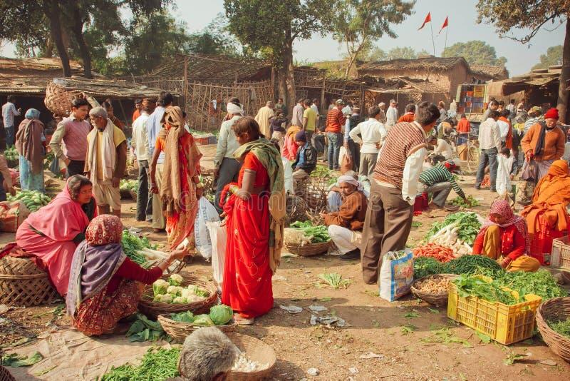 Frauen und Dorfbewohner, die Gemüse für die Familien auf billigem Dorfmarkt kaufen stockbild