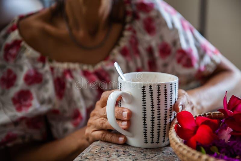 Frauen und heiße Getränke auf Händen lizenzfreie stockbilder