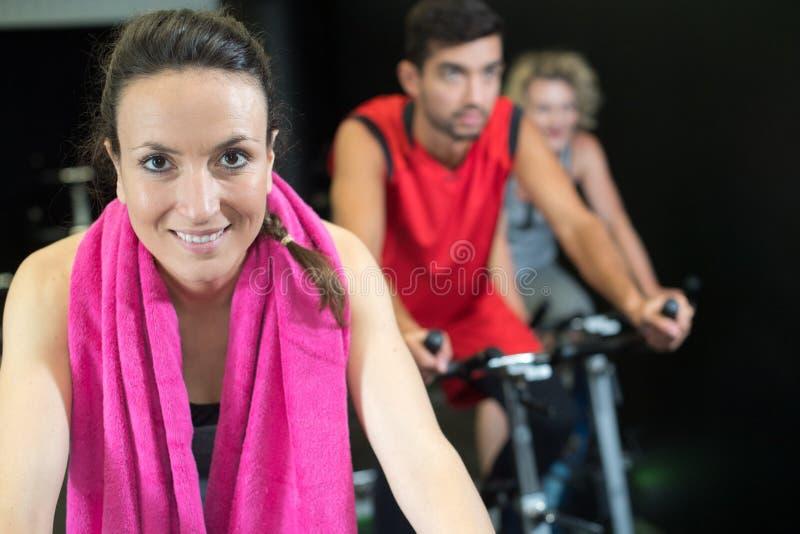 Frauen und Männer, die Fahrrad in der Turnhalle für Eignung tun lizenzfreie stockbilder