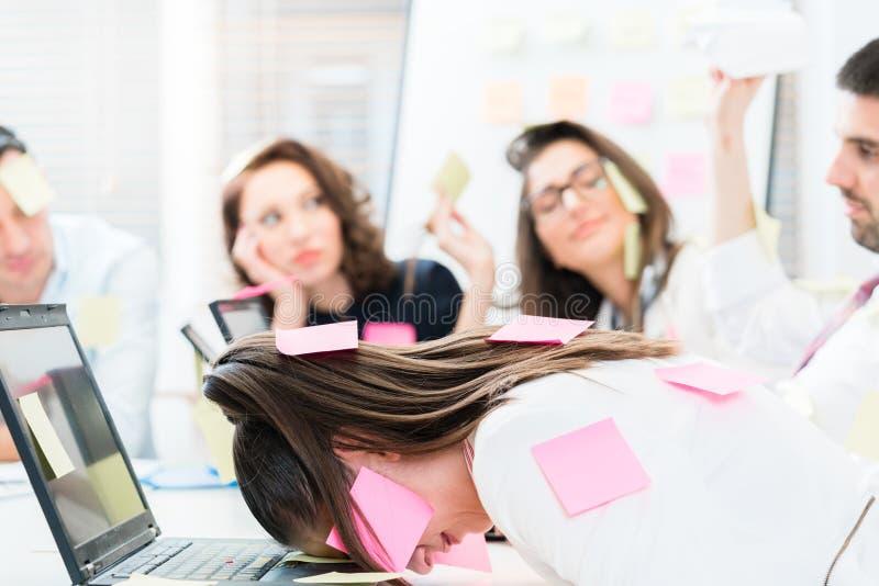 Frauen und Männer im Büro, das müde und frustriert ist stockfotografie