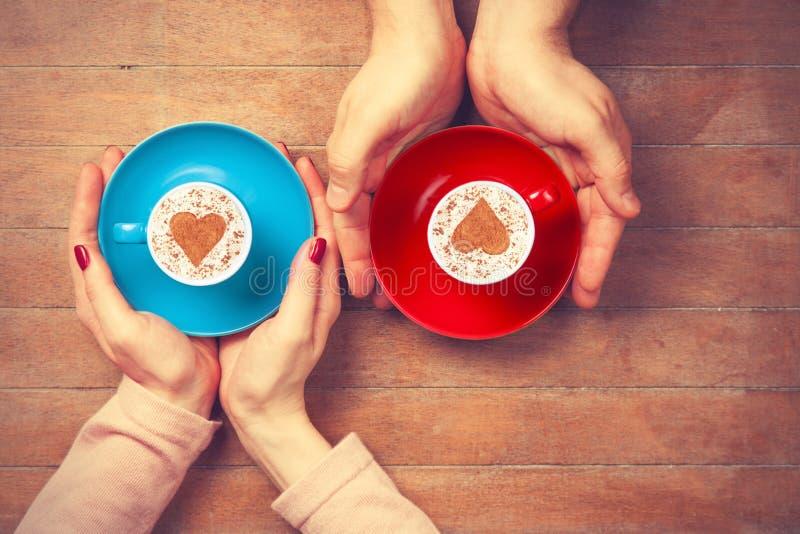 Frauen und Mann, die Tasse Kaffees halten stockfotografie
