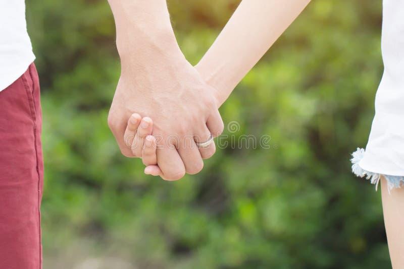 Frauen und Mann tragen einen Ring im Fingerh?ndchenhalten zusammen stockfotografie
