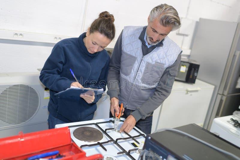 Frauen- und Mannestechniker, der Geräte in der Küche überprüft stockbilder