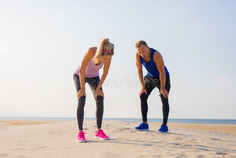 Frauen- und Manngefühl draußen ermüdet und nach Training erschöpft stockbilder