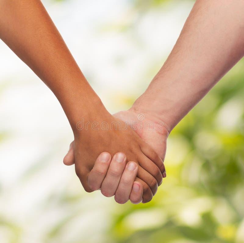 Frauen- und Mannhändchenhalten stockfotografie