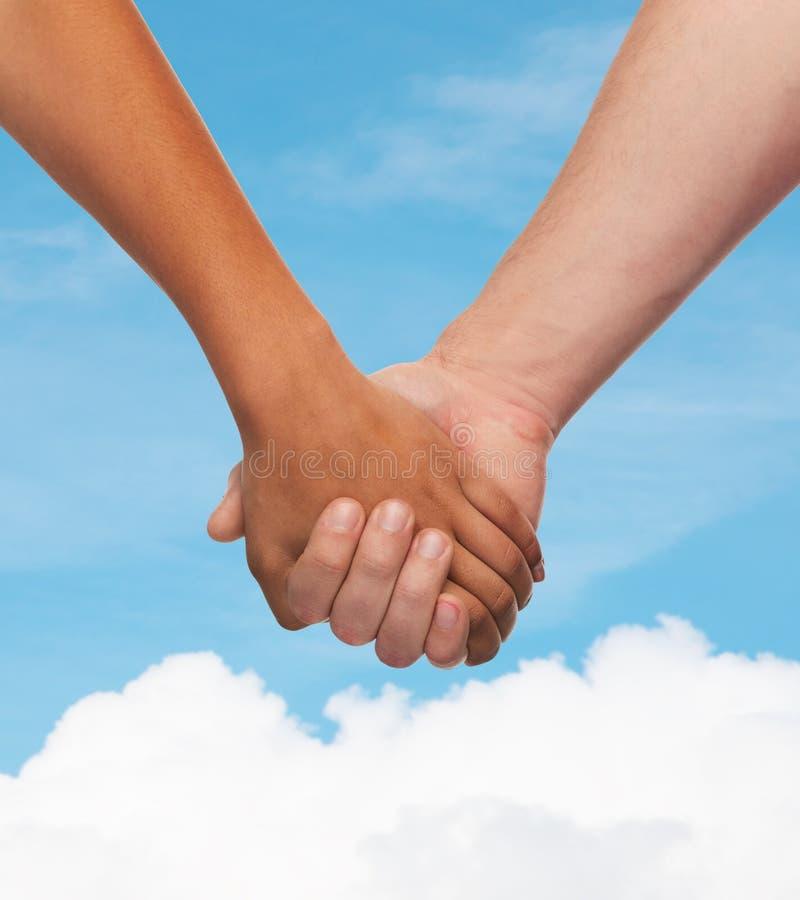 Frauen- und Mannhändchenhalten lizenzfreie stockbilder