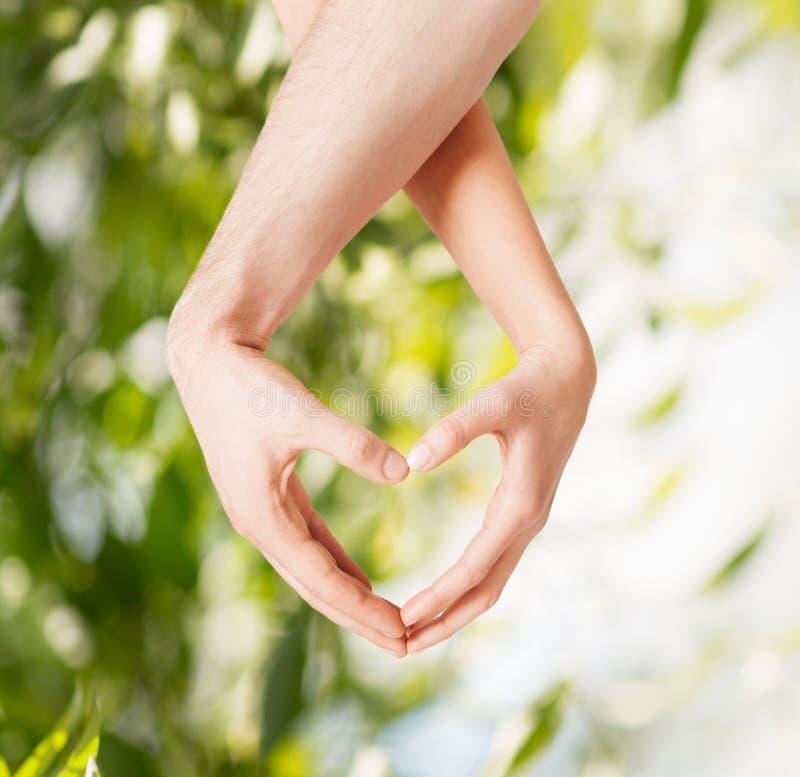 Frauen- und Mannhände, die Herzform zeigen lizenzfreie stockfotografie