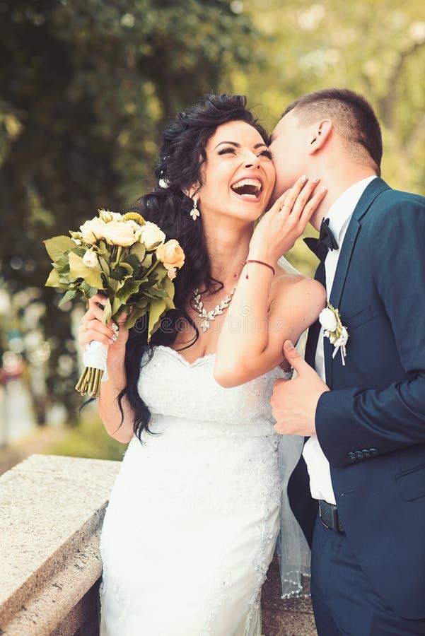 Frauen- und Mannlächeln am Hochzeitstag Glückliche Braut des Bräutigamkusses mit Blumenstrauß Hochzeitspaare in der Liebe Jungver stockfoto