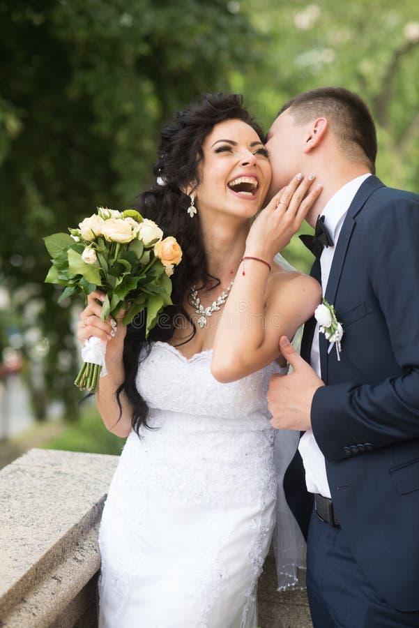 Frauen- und Mannlächeln am Hochzeitstag Glückliche Braut des Bräutigamkusses mit Blumenstrauß Hochzeitspaare in der Liebe Jungver lizenzfreies stockbild