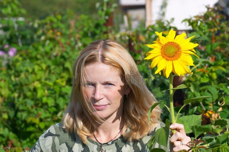Frauen und Sonnenblume. lizenzfreie stockfotografie