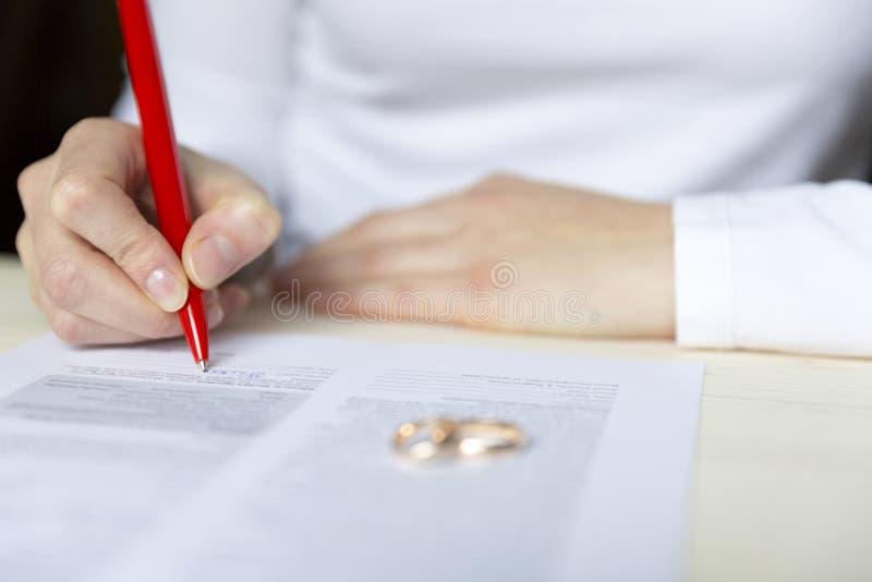 Frauen unterzeichnet Scheidungspapiere und Nehmen des Ringes stockbild
